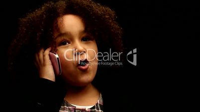 Young black girl/child with curly hair talking on mobile phone against black background 2