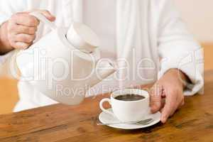 Senior mature man pour coffee wear bathrobe