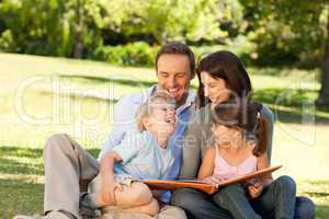 Family looking at their photo album in the park