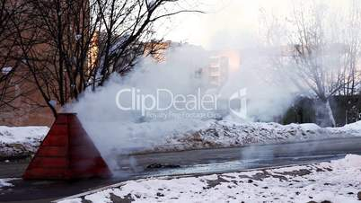 Steam on winter street from water system