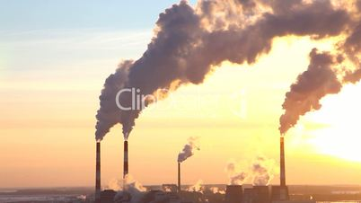 Smoke from pipe of termal power station in winter sunset