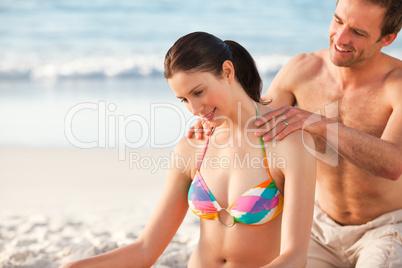 Happy man applying sun cream on his girlfriend's back