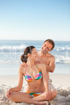 Attentive man applying sun cream on his girlfriend's back