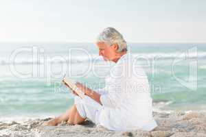 Elderly woman reading her book on the beach