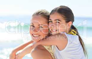 Mother having daughter a piggyback at the beach