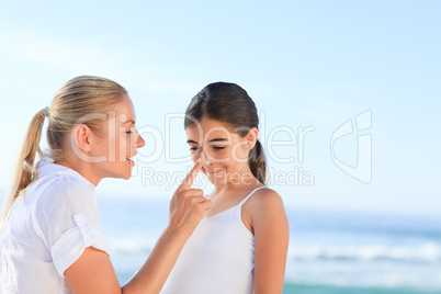 Mother applying sun cream on her daugter's nose