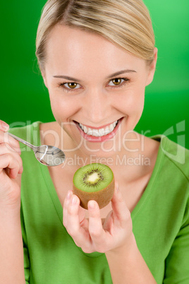 Healthy lifestyle - happy woman holding kiwi on green