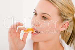 Healthy lifestyle - portrait of woman bite slice of tangerine