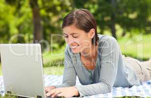 Woman working on her laptop in the park