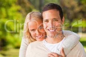 Woman hugging her boyfriend in the park