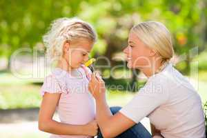 Mother and her daughter smelling a flower
