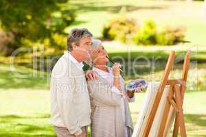 Senior couple painting in the park