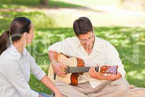 Romantic man playing guitar for his wife