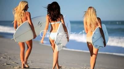 Drei Mädchen mit Surfbrettern