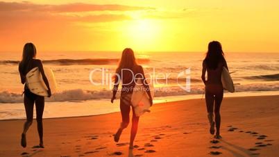 Surferinnen bei Sonnenuntergang
