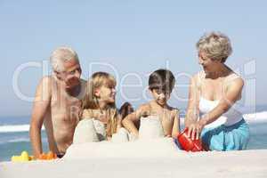 Großeltern und Kinder bauen Sandburg