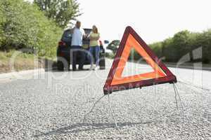 Couple Broken Down On Country Road With Hazard Warning Sign In F