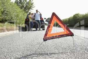 Family Broken Down On Country Road With Hazard Warning Sign In F