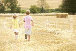 Children Running Through Summer Harvested Field