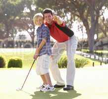 Father Teaching Son To Play Golf On Putting On Green