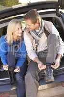 Young couple tie boots at rear of car