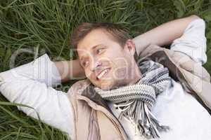 Young man lying alone on grass