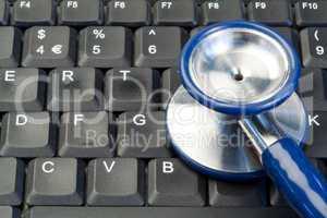 Blue stethoscope on keyboard