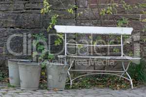 Drei Blecheimer neben einer Gartenbank