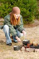 Camping woman cook food fire nature