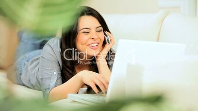 Brunette Girl at Home Using a Laptop & Smartphone
