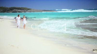Caucasian Couple Running Along Tropical Beach