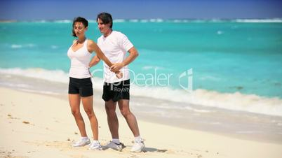 Young Couple in Sportswear Exercising on Beach
