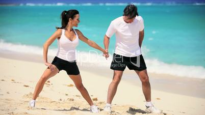 Healthy Couple Doing Muscle Stretches on Beach