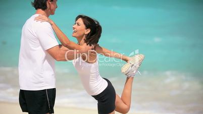 Healthy Couple Doing Exercise Stretches on Beach