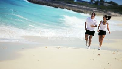 Attractive Couple Jogging Along Tropical Beach