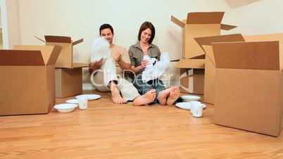 Couple Sitting on Floor of New Home