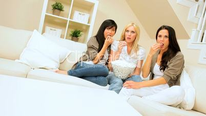 Multi-Ethnic Girlfriends Watching Scary Movie with Popcorn
