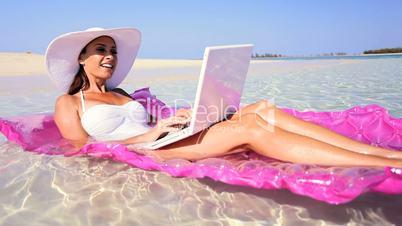 Beautiful Brunette Floating in the Ocean Using Laptop