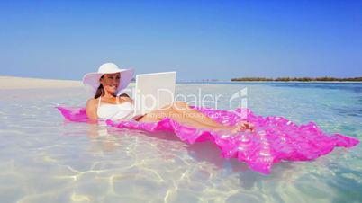 Caucasian Female Floating in the Ocean Using Laptop