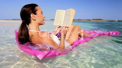 Beautiful Woman on Floating Bed with Book