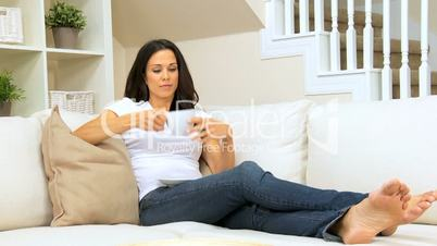 Brunette Girl on Home Couch Drinking Coffee