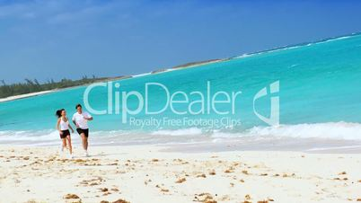 Young Couple Jogging Along Tropical Beach