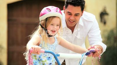 Ethnic Father Teaching Daughter on Bicycle