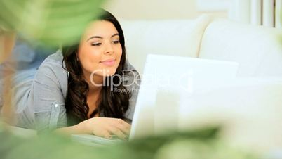 Brunette Girl Relaxing at Home Using a Laptop
