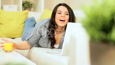 Pretty Brunette Girl Relaxing at Home with Laptop