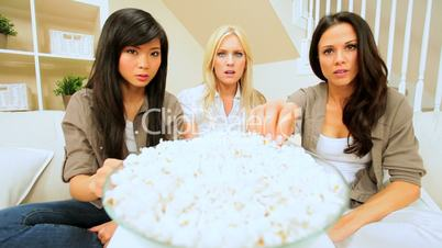 Young Girlfriends Watching Scary Movie with Popcorn