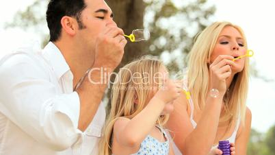 Multi-Ethnic Family Fun Blowing Soap Bubbles