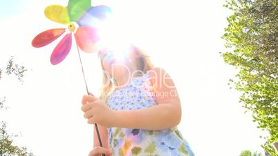 Little Girl Outdoors with Toy Pin Wheel
