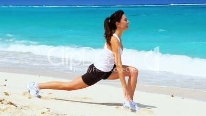 Slim Young Female Doing Stretches on the Beach