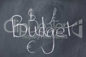 "Word ""budget"" and currencies on a blackboard"